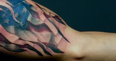 American Flag Tear Through Bicep Tattoo